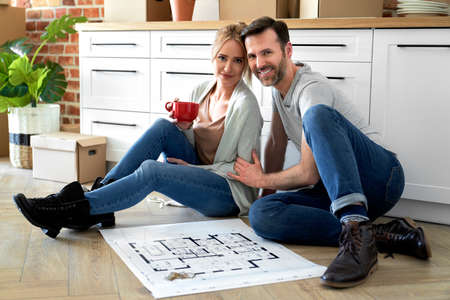 Portrait of smiling couple in their new apartment with blueprint Foto de archivo