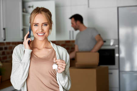 Portrait of happy woman calling and holding house keys