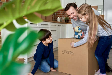 Children help their father packing cardboard boxes for the move Foto de archivo