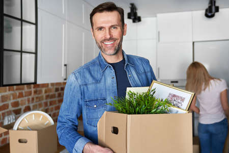Portrait of smiling man holding cardboard box during moving house
