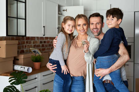 Portrait of family with children holding key for a new apartment