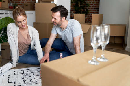 Couple sitting on the floor and planning new flat