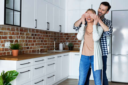 Happy man surprising woman in new flat