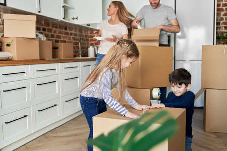 Siblings help with packing cardboard boxes for moving house