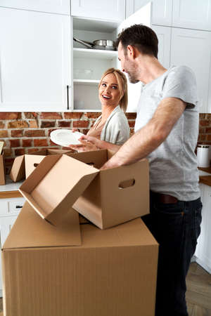 Couple during a move pack their things into cardboard boxes