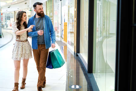 Couple with shopping bags strolling in shopping mall