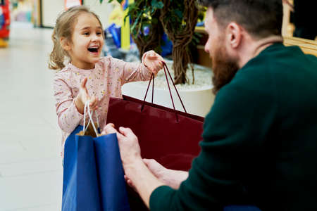 Daughter gives her dad bags full of shopping