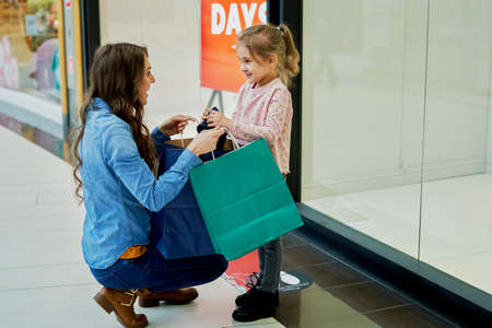 Happy mother and little daughter shopping in the mall Foto de archivo