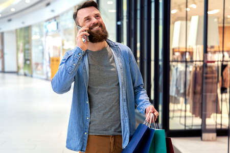 Happy man calling while shopping at the mall