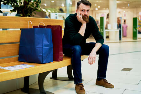 Bored man sitting on bench in shopping mall