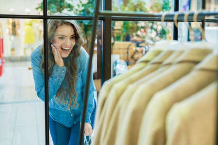 Delighted woman stalks through the shop window