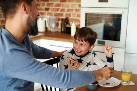 Mid adult man having breakfast with his son