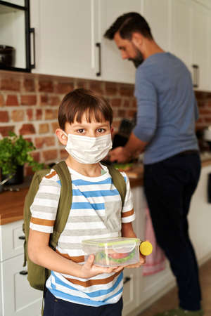 Portrait of schoolboy in protective face mask holding lunch box Foto de archivo