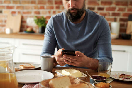 Close up of man using mobile phone during breakfast