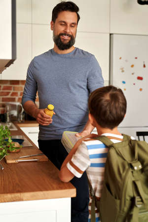 Father giving his son lunch box with healthy food