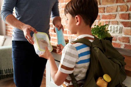 Close up of schoolboy taking lunch box and protective mask