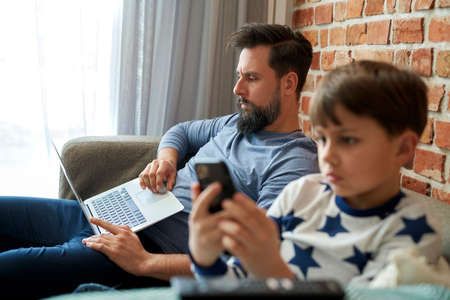 Father working on the laptop and son using mobile phone Foto de archivo