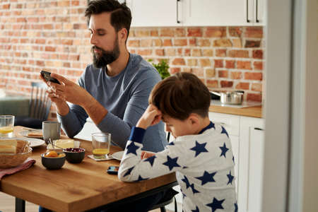 Father and son using mobile phone while breakfast