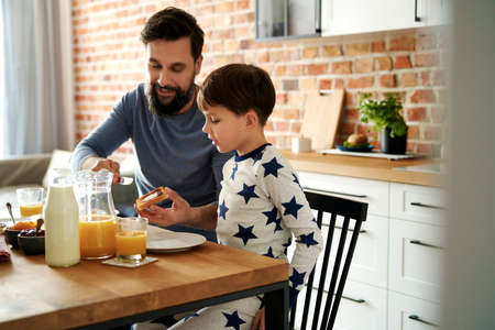 Happy father and son having breakfast together at the morning
