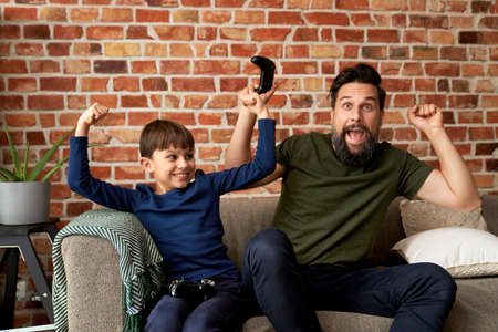 Father and son have fun while playing video game