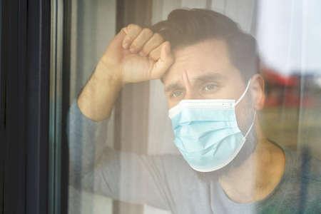 Close up of man on quarantine looking through the window