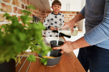 Close up of father preparing breakfast cereal