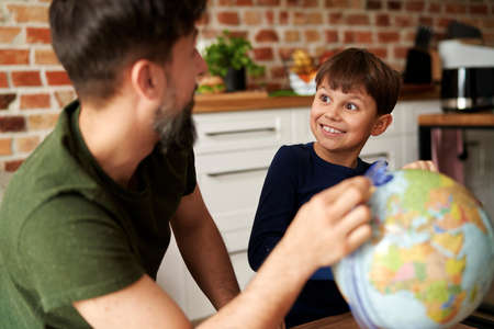 Happy father and son looking at globe of the world
