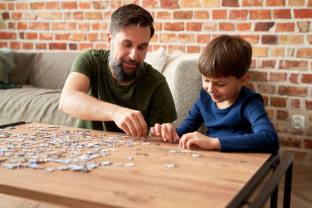 Boy solving jigsaw puzzle with father in living room at home