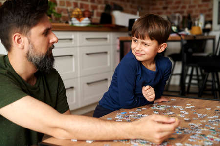 Father and son sitting and solving jigsaw puzzle