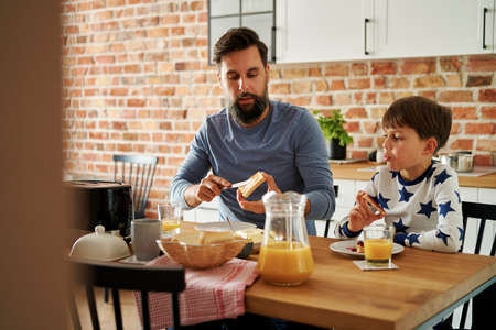 Father and son eating breakfast together at the morning