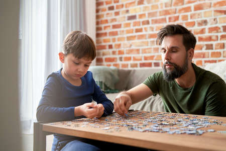 Father and son solving jigsaw puzzle together at home