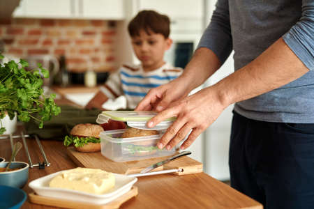 Close up of father making lunch box for son