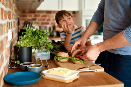 Close up of father making lunch for son in kitchen