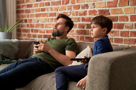 Father and son watches TV together at home Foto de archivo
