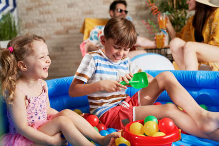 Laughing children having fun in an inflatable ball pool