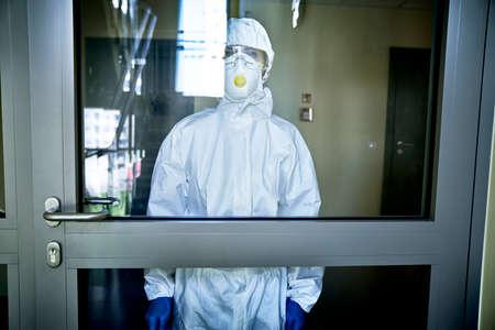 Person in a hazmat suit disinfecting in front of the door
