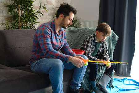 Single father and son playing fishing at home