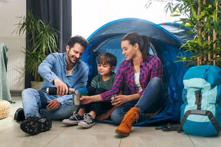 Family sitting next to the tent while camping at home