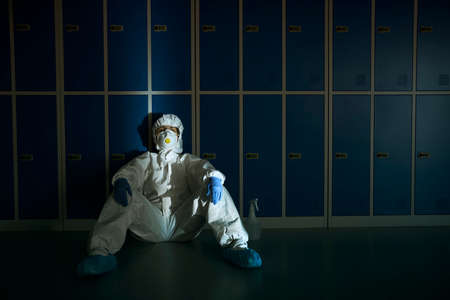 Overworked healthcare worker sitting close to the locker