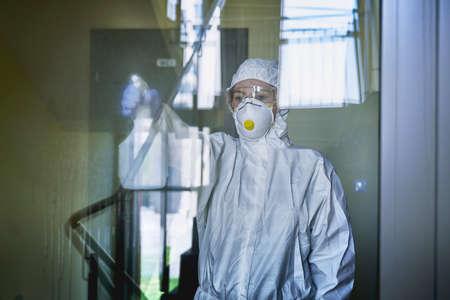 Woman in protective suit disinfecting door in the public building
