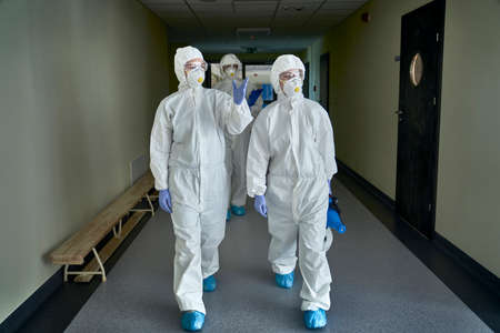 Group of technicians in protective workwear while inspecting the building Фото со стока