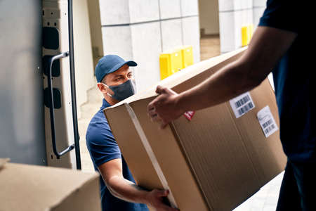 Close up of couriers unloading packages from a delivery truck