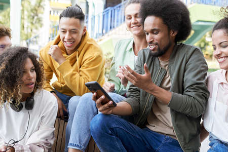 Group of smiling young friends sitting together with mobile phone Фото со стока
