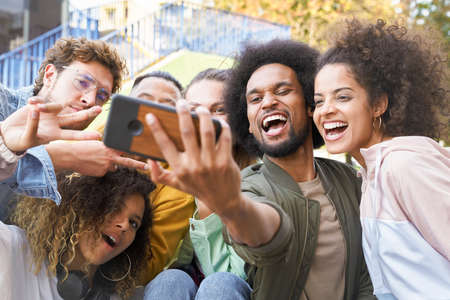 Group of happy young people doing selfie together outdoors