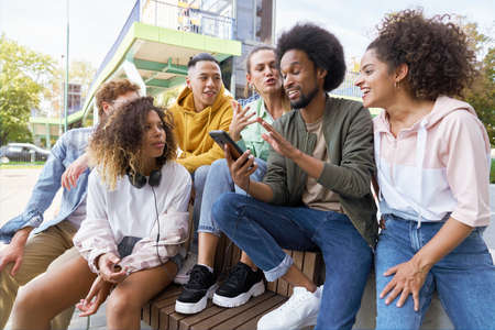 Group of young friends sitting and talking together with mobile phone