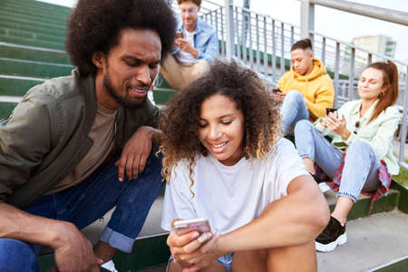 Young people sitting with your mobile phones outdoors