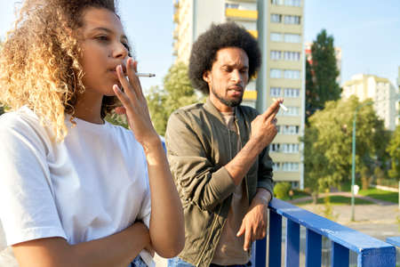 Two young people standing and smoking cigarette