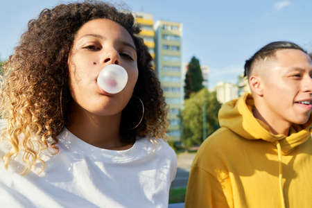 Young couple outdoors and woman making bubble gum balloon