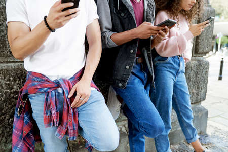 Close up of unrecognizable young people standing with mobile phones