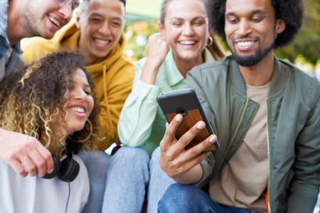 Close up of group of happy people sitting with phone Фото со стока